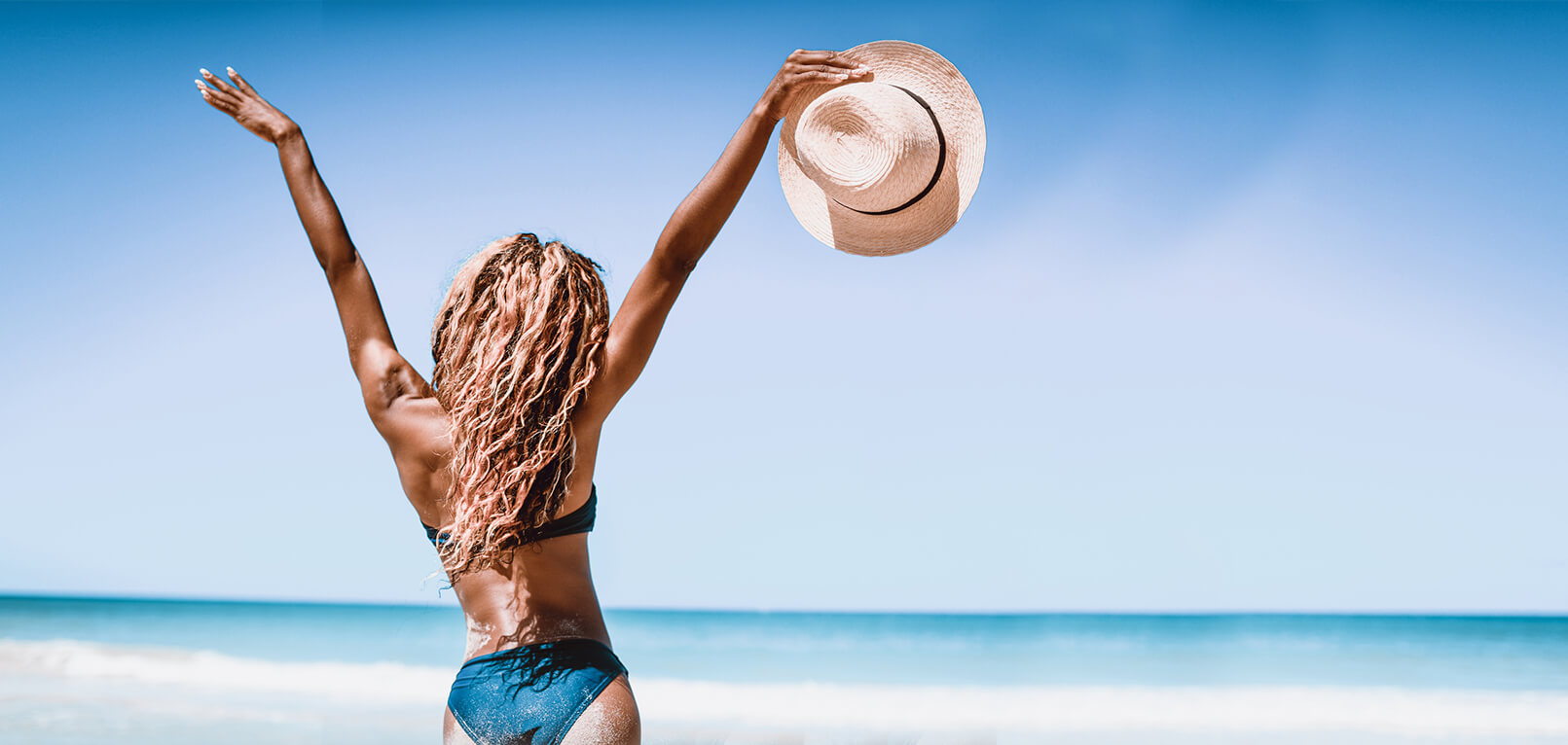 Woman at beach with her arms in the air