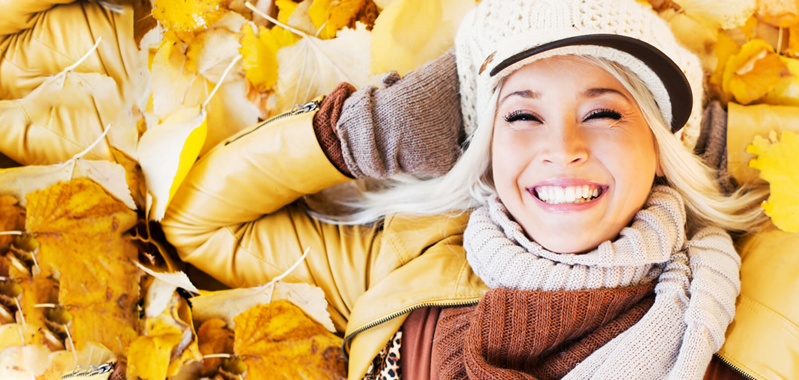 woman smiling laying in leaves